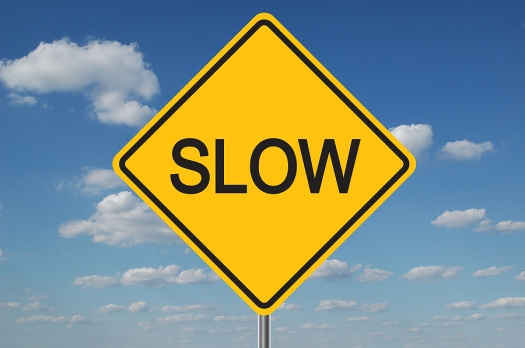 bigstock-Slow-Traffic-Sign-With-Clouds-1373892