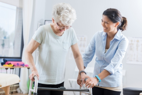 Healthcare professional helps senior woman walk with a walker